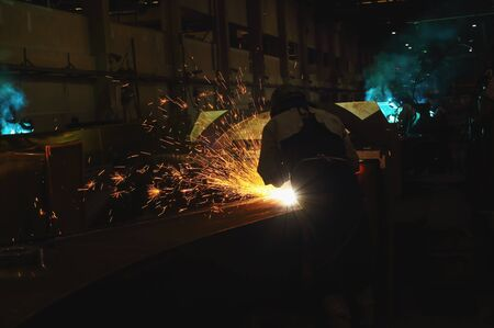 fireproof: Welder arc Gouging carbon electrode rods   with sparks and smoke in  factory