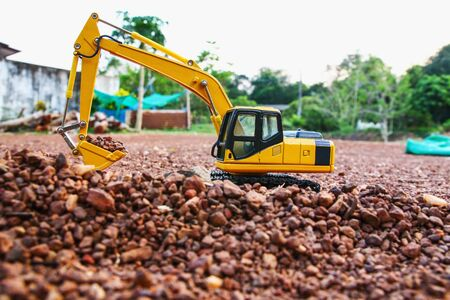 Excavator loader model on ground and  are digging stone Stock Photo