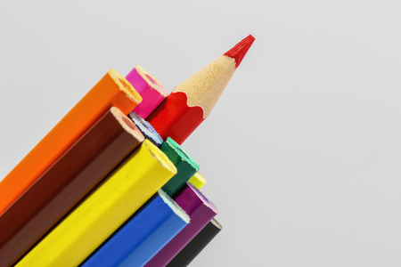 Set of colored pencils with a single sharp one symbolizing leadership concept