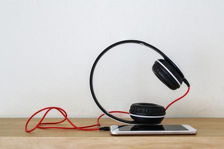 Headphones  and smartphone on wood floor background ,Concept listen to music