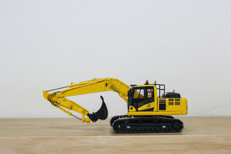 Crawler Excavator model on wooden floor with wall background