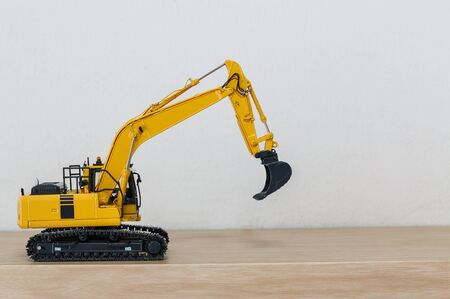 Crawler Excavator model on wooden floor with wall white background