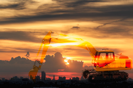 Excavator loader model with Silhouette on sunset at city building background,Concept  Double exposure Stock Photo