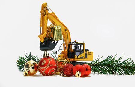 Weihnachtszierde und Bagger Modell, Feiertagsfeierkonzept neues Jahr auf weißem Hintergrund