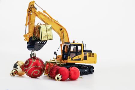 Regalo de Navidad con el modelo del excavador, año nuevo del concepto de la celebración del día de fiesta en el fondo blanco