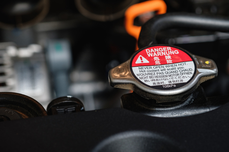 Engine radiator cap with warning labels in  sealed and safety first