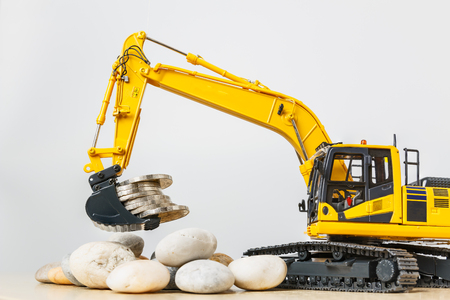Excavator  model  with a money save concept, in  bucket  lift up on white background