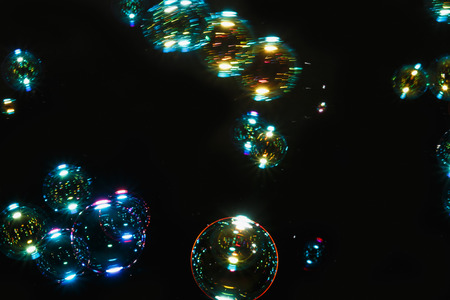Blurred  soap bubbles colorful  with  on dark  backgrounds.