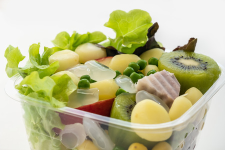 Salad of fresh vegetables and healthy grains, In clear plastic box,On a white background