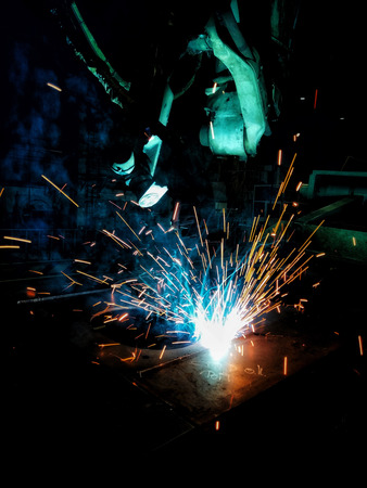 Welding Sparks and smoke from robot welding in industrial manufacturing Imagens