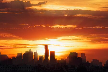 Sun rays  with cityscape of building silhouette,At  twilight  in Bangkok ,Thailand