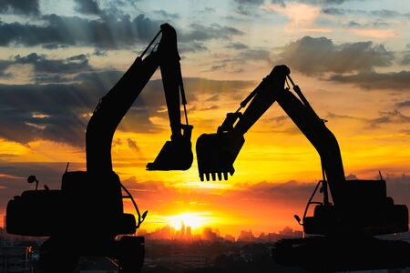 Two Black silhouette of backhoe loader with sunset light background,In cityscape