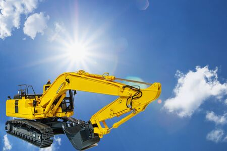 Yellow excavators on the sky and sunlight background