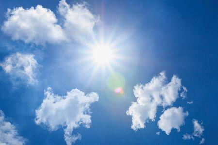 Raggi di sole che splendono attraverso le nuvole bianche con il blu in estate