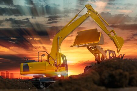 Excavators and wheel loader are digging the soil in the construction site on the sunset background