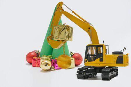 Ornamento de Navidad y modelo de excavadora, concepto de celebración navideña año nuevo en blanco Foto de archivo