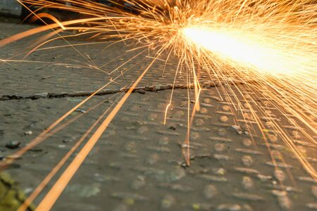 Grinding sparks of tools on steel in factory with manufacturing