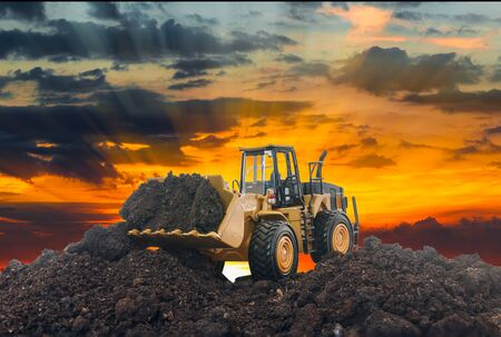 Wheel loader are digging the soil in the construction site on the sunset Stock Photo