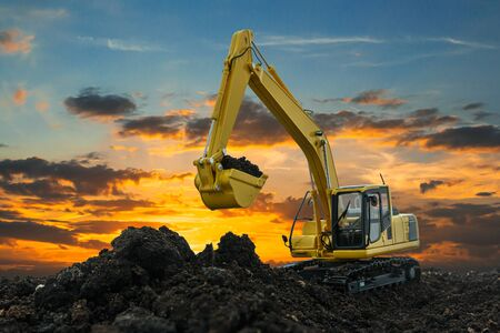 Excavators are digging the soil in the construction site on the sunset sky background