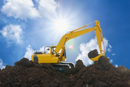 Yellow excavators are digging the soil in the construction site on the sky and sunbeam background
