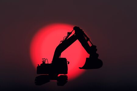 Silhouette image excavators loaders on a red sunset background Фото со стока