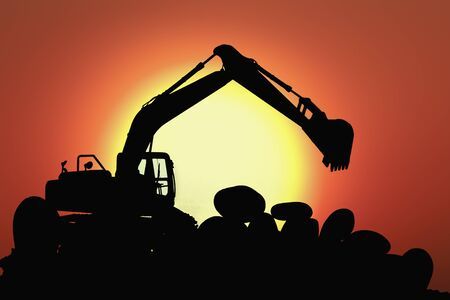 Excavators silhouette are digging the soil in the construction site on the  sunset sky background