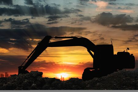 Black silhouette of backhoe loader with sunset light background,In cityscape 版權商用圖片
