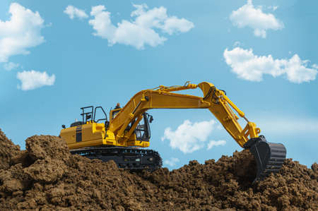 Yellow excavators are digging the soil in the construction site on the cloud and sky background