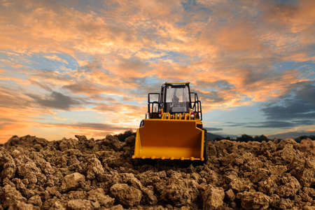 Wheel loader are digging the soil in the construction site on the  sunset background