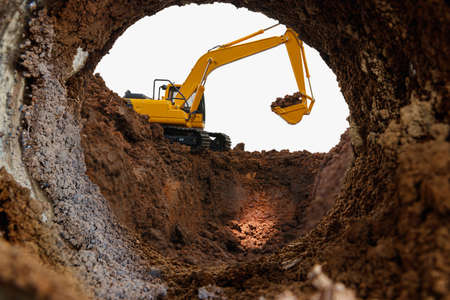 Crawler excavator are digging soil in the tunnel construction site.