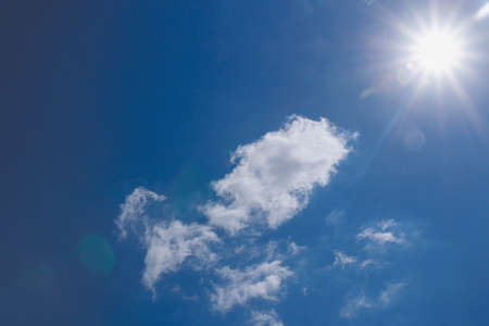 Sunbeams in summer with  white clouds on a blue sky background