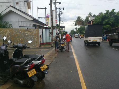 Fußgänger helfen dem Motorradfahrer auf der Straße Editorial