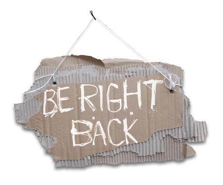 Kartonnen bord aan een koord met de woorden BE RIGHT BACK. Gescheurd, gegolfd papier opknoping op koord met wit teken BE RIGHT BACK.Isolated op een witte achtergrond.
