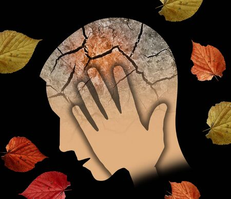 Autumn sadness and depression, young man. Stylized Male Head Silhouette Holding His Head.Photo-montage with Dry Cracked Earth and Autumn Leaves Symbolizing Depression. Stock Photo