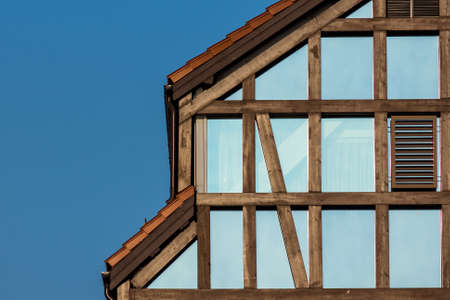 fachwerk: Fragment of a half-timbered house made of glass on a background of clear blue sky Stock Photo