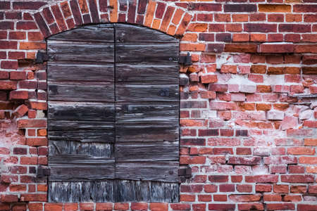 crumbling: Fragment of a warehouse with crumbling brick wall and old wooden shutters closed