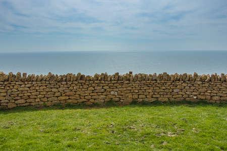 cuatro elementos: Exposición horizontal de cuatro elementos: el prado verde, muro de piedra, mar azul y el cielo