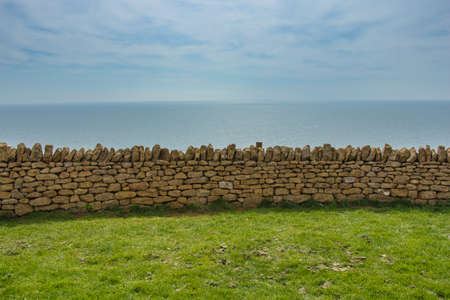 four elements: Horizontal exposition of four elements: green meadow, stone wall, blue sea and the sky