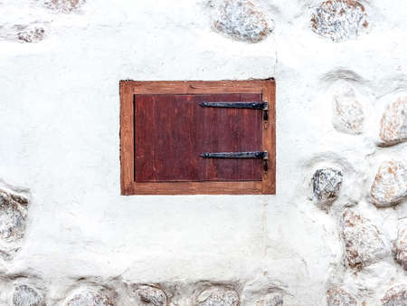 hinges: Closed window with shutters on the old style metal hinges. White uneven wall with fragments of stones visible