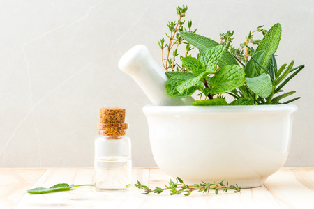 Alternative health care fresh herbal and  Bottle of aromatherapy in mortar on wooden background.