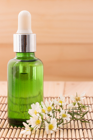 Bottle serum for beauty Spa and therapy treatment with wildflowers on wooden background.