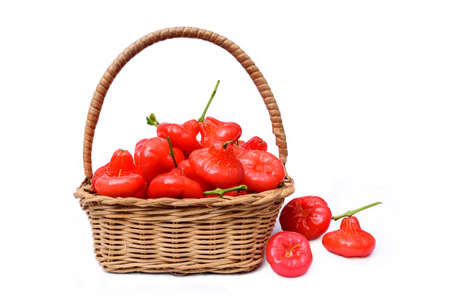 Wicker basket filled with red fruits, isolate on white background Stock Photo
