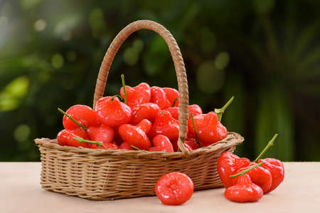 Wicker basket filled with red fruits Stock Photo