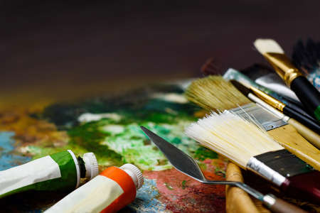 Palette knife and paint brushes in the basket with color tubes on the old palette
