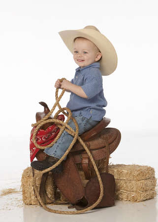 little cowboy riding in saddle photo