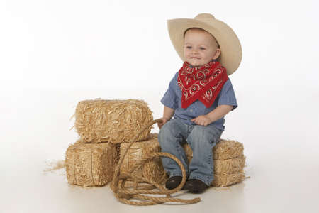 little cowboy on bales of hay