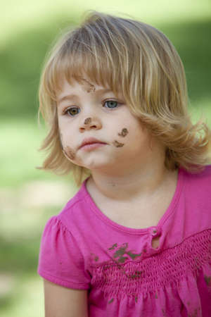little girl with mud on her face photo