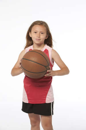 youth sports: little girl on white holding a basketball
