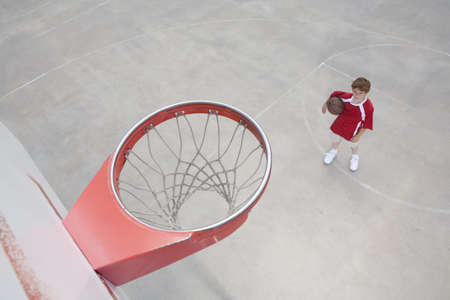 1 person: Boy standing looking up on basketball court