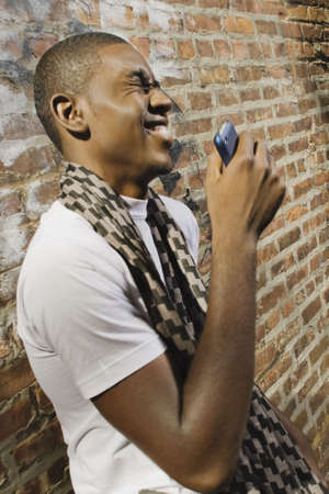 A young African American man on the phone in an urban environment. 스톡 콘텐츠